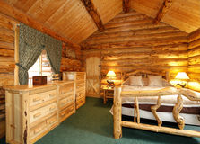 Cozy bedroom in log cabin house Stock Photo