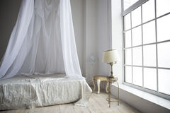 A cozy bedroom in pastel colors with a large bed, a table lamp o Royalty Free Stock Images
