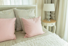Cozy bedroom with pink pillows and reading lamp on beds Royalty Free Stock Photo