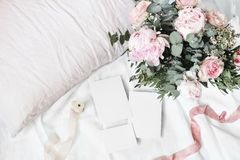 Cozy bedroom still life scene. Wedding, birthday bouquet of pink roses, peony flowers and eucalyptus branches. Silk. Ribbons on linen bedding. Blank greeting stock photos
