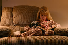 Cozy Bedtime Reading. A little girl curled up on a comfy chair before bed with her dog and a favorite book