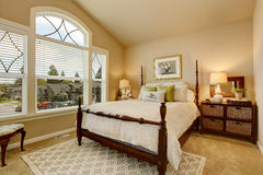 Cozy Beige bedroom with vaulted ceiling and elegant Victorian style bed. Stock Images