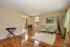 Cozy beige sitting room with shiny hardwood floor and dining area Royalty Free Stock Photo