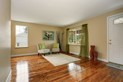 Cozy beige sitting room with shiny hardwood floor and green curtain Royalty Free Stock Images