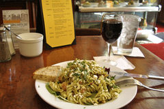 Cozy bistro/cafe table with red wine and pasta salad Stock Photography