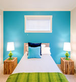 Cozy blue and green bedroom. Interior design. Modern blue bedroom interior in a luxury house with reclaimed wood bedside tables Royalty Free Stock Images
