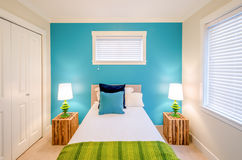 Cozy blue and green bedroom. Interior design. Modern blue bedroom interior in a luxury house with reclaimed wood bedside tables Stock Photography