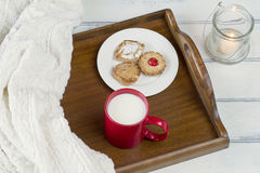 Cozy breakfast. Comfortable homey scene: Some cookies on a plate, a red mug with milk on a tray and a candle Royalty Free Stock Photo