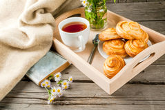 Cozy breakfast with freshly baked scones. Cozy breakfast in spring or early autumn tea, freshly baked scones and bouquet of field's daisy. Notepad for taking Royalty Free Stock Photo