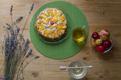 A cozy breakfast at home early morning consist of a biscuit homemade cake decorated with pieces of peach and plum and the bouquet. A cozy homemade breakfast Royalty Free Stock Image
