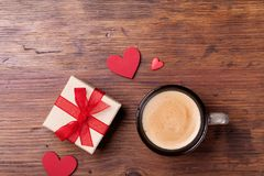 Cozy breakfast for Valentines day. Coffee, gift or present box and red heart on rustic wooden table top view. Cozy breakfast for Valentines day. Coffee, gift or Stock Image