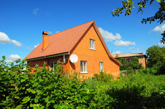Cozy Brick House with Old faded red metal roof tile and chimney outdoor. Bad Roofing Exterior. Royalty Free Stock Photos
