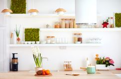 Cozy bright kitchen with wooden countertop and island cooker hood Royalty Free Stock Image