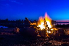 Cozy camping fire with flame edged with stones on german danube stock images
