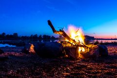 Cozy camping fire with small flame edged with stones on german d royalty free stock photography