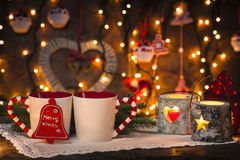Cozy christmas. Christmas decorated set up of candles and two coffee mugs on a rustic wooden table with blured xmas lights and decoration on the background Stock Photos