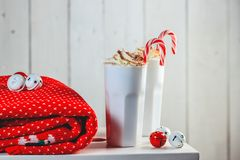 Cozy Christmas composition.Two mug with hot drinks, chocolate with whipped cream and Candy Canes in front of a light wooden backgr. Ound. Sweet treats for cold royalty free stock photo