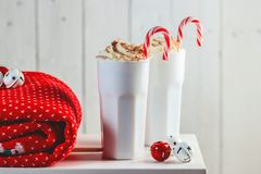 Cozy Christmas composition.Two mug with hot drinks, chocolate with whipped cream and Candy Canes in front of a light wooden backgr stock photography