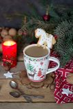 Christmas composition with a mug of coffee, gingerbread horse, with a candle, fir branches and Christmas decorations. stock photos