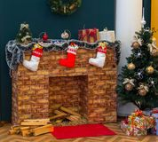 Cozy Christmas corner with fireplace, Christmas tree and gifts royalty free stock photos