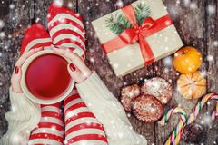 Cozy Christmas at home. Female hands holding a cup of tea, Women`s feet in Christmas stockings, big present Royalty Free Stock Photography
