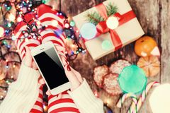 Cozy Christmas at home. Female hands holding mobile phone. Women`s feet in Christmas stockings, big present on bokeh light backgr. Ound. Top view. Selective Royalty Free Stock Photo