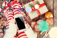 Cozy Christmas at home. Female hands holding mobile phone. Women`s feet in Christmas stockings, big present on bokeh background. Cozy Christmas at home. Female Stock Photos