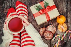 Cozy Christmas at home. Women`s feet in Christmas stockings, big present, cup of tea, candy and Cookies Chocolate on bokeh light b. Ackground. Top view Royalty Free Stock Images