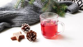 Cozy Christmas morning breakfast scene. Steaming glass cup of hot fruit red tea standing near . Pine cones, wooden star stock video footage