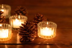 Cozy christmas table decoration, candles and pine cones. stock images