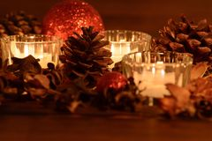 Cozy christmas table decoration, red christmas balls and pine cones royalty free stock images