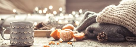 A cozy Christmas tea Cup still life. Details of still life in the home interior living room. Beautiful Cup of tea with tangerines and sweaters on wooden Royalty Free Stock Photo