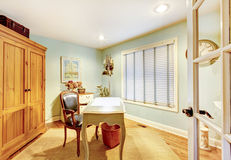 Cozy classic home office with green wall, carpet and small empty desk. Royalty Free Stock Photo