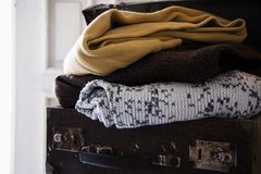 Cozy clothes in an antique suitcase. Vintage cozy clothes in an antique suitcase, copy space Royalty Free Stock Photography