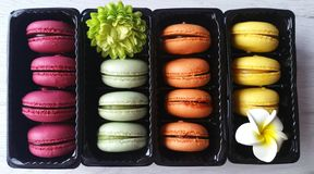 Cozy colorful macaroons. Macaroons in pretty colors in dark boxes on white wooden background Stock Photography