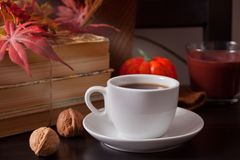 Cup of coffee, autumn leaves, pumpkin, books on the wooden table. Autumn harvest. Autumn concept