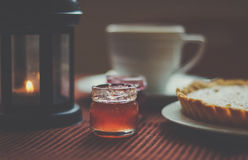 Cozy composition. Pumpkin tart, black tea, cherry and strawberry jams and christmas candlestick Royalty Free Stock Photos