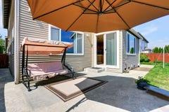 Cozy concrete floor patio area at the backyard garden swing Royalty Free Stock Image