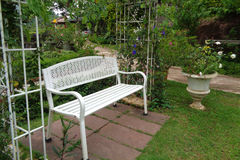 Cozy Corner in the Backyard with a white Iron Bench Stock Image
