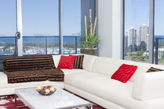 Cozy corner couch. With red and brown cushions in an apartment with big windows Stock Photos