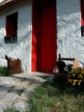Cozy cottage with red door. A view of a cozy little white cottage with a bright red door and curved stone walkway leading to the entrance Royalty Free Stock Photography