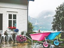 Cozy country house terrace exterior. With flowers, table and colorful garden trolley mountains view Stock Image