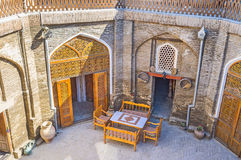 The cozy courtyard. The tiny cafe in the shady courtyard of the restored Caravan Saray is the best place to relax, Bukhara, Uzbekistan Royalty Free Stock Image