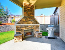 Cozy covered patio interior with stone trim fireplace and barbecue. Royalty Free Stock Photo