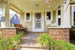 Cozy covered porch with white columns in American craftsman house Stock Images