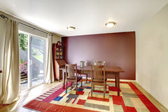 Cozy dining room with brown wall and wooden table set. Royalty Free Stock Photo