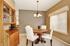 Cozy dining room with white chairs and vintage round table. Royalty Free Stock Image