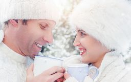 Cozy dressed couple drink hot tea on snow forest glade Stock Images