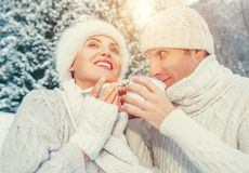 Cozy dressed couple in love drink hot of tea in winter forest royalty free stock images
