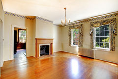 Cozy empty living room with fireplace and hardwood floor. Royalty Free Stock Images
